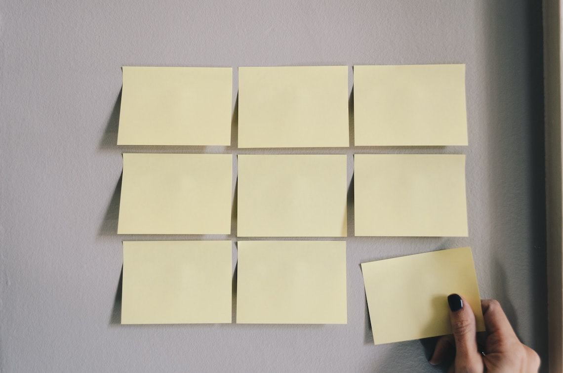 A photo of sticky notes laid out in a 3x3 grid pattern